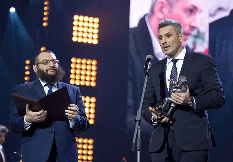 Yan Vizinberg, a partner at Lorem Ipsum, accepts the Fiddler on the Roof award for the company's work on this experiential design project.